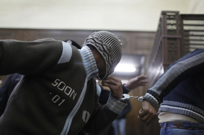 Defendants enter a cell a few minutes before they hear the verdict at a court in Cairo